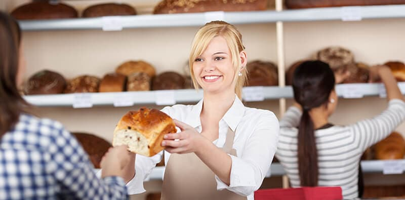 Woman holding a bread in a bakery
