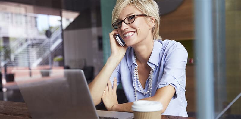 Woman with blonde hair and glasses smiles and speaks on the phone