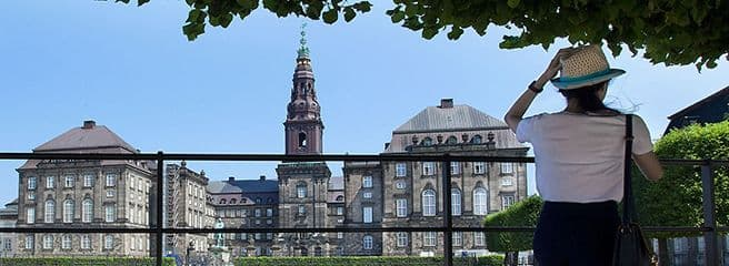 Christiansborg seen from the outside with a woman standing with her back to the camera and looking at the castle