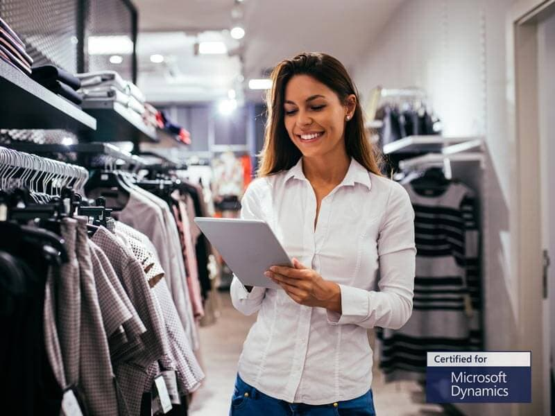 Woman holding tablet in clothing store using Microsoft Dynamics