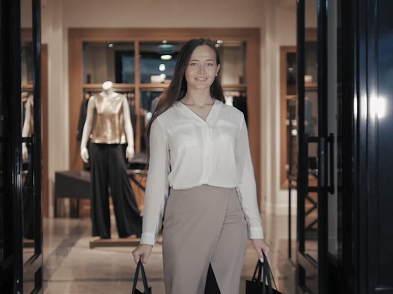Woman with dark hair stands with two bags and smiles
