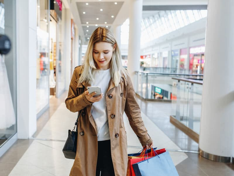 Woman with shopping bags checking her phone