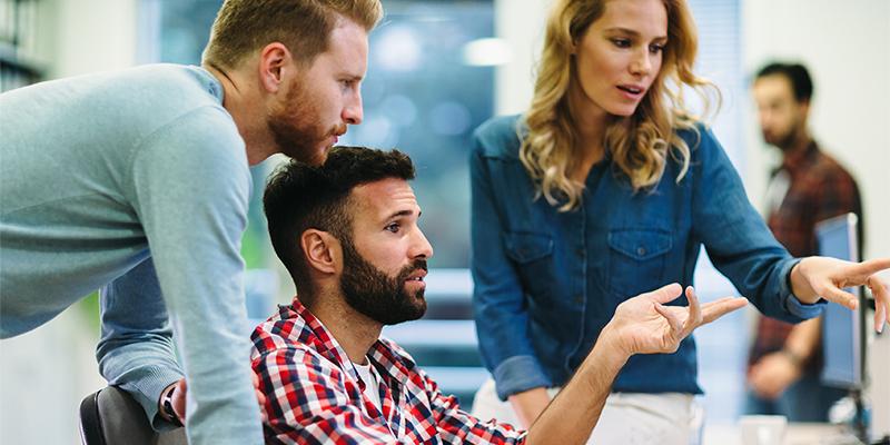Retail-konsulent diskuterer med to kollegaer