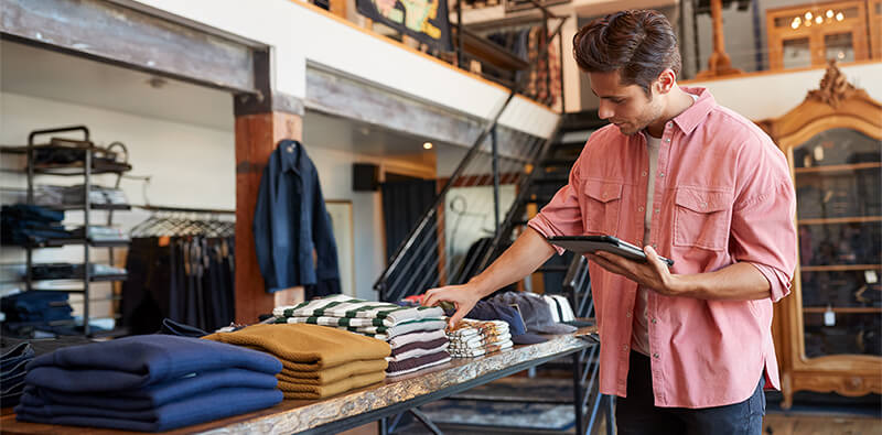 Man in clothing store with tablet is conducting inventory management