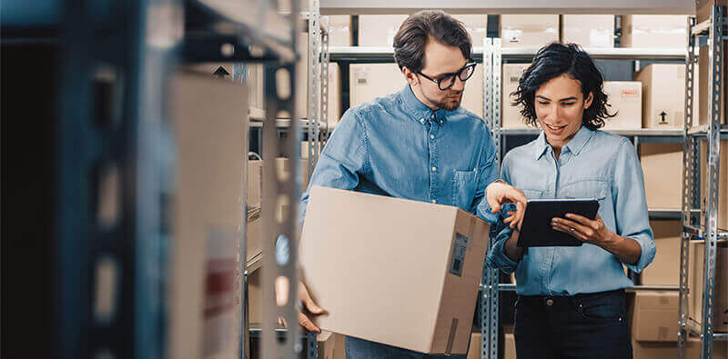 Man and woman working in warehouse and controlling inventory management
