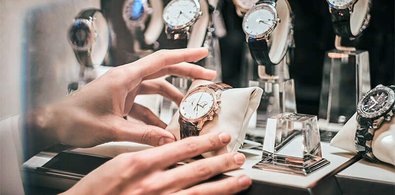 Hand placing a watch in the store